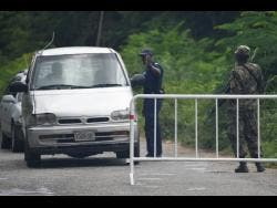Jamaica Defence Force and police personnel man a checkpoint in Sevens Heights, Clarendon, on Thursday.