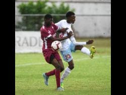 Eltham High School's Dontae Brown (left) challenges St George's College player Malique Dawes during their ISSA/Digicel Manning Cup encounter at Winchester Park on Monday.