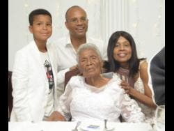 Centenarian Dorothy Austin (seated) celebrates with great-grandson Tristan Jennings (left), grand-daughter Tracy Lake (right) and her spouse, Shawn Jennings, at the Medallion Hall Hotel in Kingston on Saturday.
