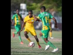 Clive Beckford of Charlie Smith (left) goes on the attack against Vindiesel Isaacs of Kingston High school in their ISSA/Digicel Manning Cup fixture played at Breezy Castle on September 14.