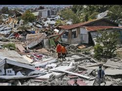 Rescuers carry a body bag containing the remains of an earthquake victim through a neighbourhood flattened by the disaster in Palu, Central Sulawesi, Indonesia.