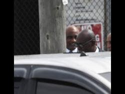 Ruel Reid (right) and Dr Fritz Pinnock (background) emerge from the Kingston and St Andrew Parish Court yesterday after receiving bail.