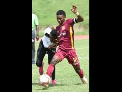 Wolmer's Boys School captain Shamour McLean shields the ball from Tarrant High School's Aidiair Tate at the Stadium East field on October 8.
