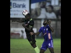 Molynes United player Renaldo Smith (left) heads the ball away from Mount Pleasant's Francois Swaby in their Red Stripe Premier League encounter at Drewsland on October 6, 2019.