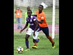 Kingston College's Arymanya Rodgers (left) dribbles away from Dunoon Technical's Omari Morgan during their ISSA/Digicel Manning Cup encounter at the Stadium East field on Monday, September 10, 2018.