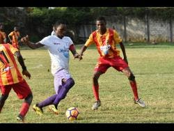 Andre Tate of Irwin High School (centre) tries to dribble past Calvin Gardener of Cornwall College in their  ISSA/WATA daCosta Cup encounter at the Cornwall playing field in Montego Bay last season.