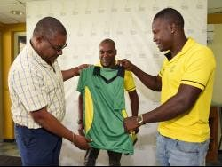 Courtney Francis (left), CEO of the Jamaica Cricket Association, hands over the Jamaica Scorpions 2019-20 kit to captain Rovman Powell (right) as coach André Coley looks on during a press conference at Sabina Park yesterday.