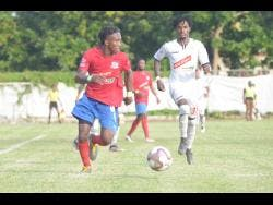Dunbeholden forward Demario Phillips (left) dribbles as UWI defender Damano Solomon tries to close him down during their Red Stripe Premier League fixture at the Royal Lakes field in St Catherine on October 27.
