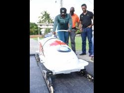 Bobsledder Carrie Russell (left)  shows off her pushing skills to Denzil Wilks (centre), general manager of the Sports Development Foundation (SDF), and Christian Stokes (right), president of the Jamaica Bobsleigh and Skeleton Federation, during a training session at G.C. Foster College yesterday.