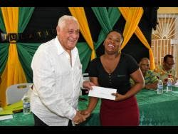 Central Clarendon MP Mike Henry presents a cheque to University of the Commonwealth Caribbean student, Nackeisha Francis.