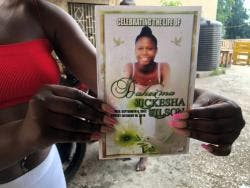 Tessa Wilson displaying her sister's funeral programme.
