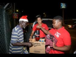 D'Angel and her son Marco Dean (right) present Earl with the goodies they bought to help make his Christmas a little brighter.