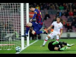 Barcelona's Lionel Messi leaps over Mallorca's goalkeeper Manolo Reina, on the ground, during a Spanish La Liga match between Barcelona and Mallorca at Camp Nou stadium in Barcelona, Spain, last Saturday.