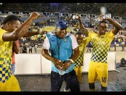 Lenworth Hyde (centre), coach of Clarendon College, is doused with water by members of the team as they celebrate retaining the Olivier Shield.