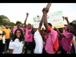 Shelly-Ann Fraser-Pryce presents the winning trophy to Legacy United at the Shelly-Ann Fraser-Pryce Six-A-Side final at Foska Oval at 451 Spanish Town Road in Kingston, yesterday.