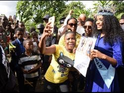 Toni-Ann Singh (right) poses for pictures with fans  in Arcadia, St Thomas, yesterday.