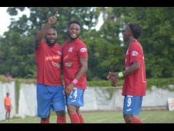 Dunbeholden's goal scorer Dean Andre Thomas (centre) celebrates with teammates Andre McFarlane (left)  and Demario Phillips (right) after finding the back of the net against UWI FC on October 27, 2019.