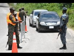A Jamaica Defence Force personnel mans a checkpoint in Whitehouse, Westmoreland last year after the state of public emergency was declared for the parish.