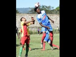 Humble Lion's Mark Rodney (left) is outjumped by Portmore United's Shai Smith (right) during their Red Stripe Premier League match which was played at the Spanish Town Prison Oval on Sunday.