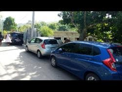 Photo shows a number of vehicles parked outside the home of Rajui Brown, the man who allegedly shot himself to death at Binns Lane in Elgin Town, Hanover, last Saturday.