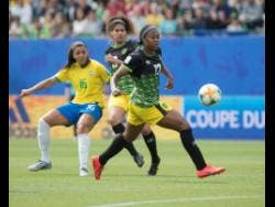 Allyson Swaby (right) makes a pass ahead of teammate Marlo Sweatman (centre) and Beatriz Zaneratto Joao of Brazil during the Jamaica versus Brazil match at the FIFA Women's World Cup 2019 at the Stade des Alpes in Grenoble, France, on Sunday, June 9, 2019.  Brazil won 3-0.