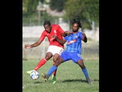 UWI FC's  Ryan Miller (left) attempts a shot at goal while under pressure from Dunbeholden's Shevan James during the  Red Stripe Premier League encounter at the UWI Bowl last Sunday. The game ended 0-0.