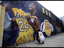 A fan pays respects at a mural depicting Kobe Bryant in a downtown Los Angeles alley after word of the Lakers star's death in a helicopter crash, in downtown Los Angeles yesterday.