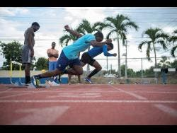 Jamaica College's sprinters Jonathan Henry (foreground) and Christopher Scott launch out of the starting block during a training session at the Ashenhiem Stadium on their school compound as they prepare for the 2020 ISSA/GraceKennedy Boys and Girls' Athletics Championships.