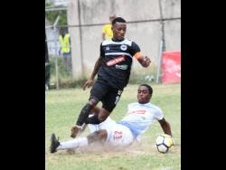 Emilio Rousseau (right) of Portmore United puts in a sliding challenge on Chevone Marsh of Cavalier during a Red Stripe Premier League match on Sunday, February 10, 2019.