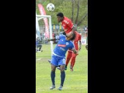 Stephen Barnett (right) from UWI F.C. outjumps and heads the ball away from Kemar Beckford (left) from Mount Pleasant F.C.