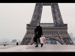 A masked couple walks on the empty Trocadero next to the Eiffel Tower, in Paris, France.