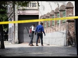 Members of the Jamaica Constabulary Force examine the crime scene where an alleged thief was shot dead on Monday on East Parade in the vicinity of the Coke Memorial Methodist Church.