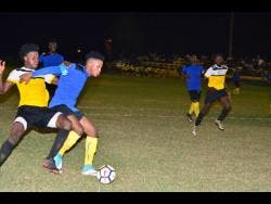 Tevoy Colespring (second left) of Meadforest FC holds off Barbican FC's Damian English during their Magnum KSAFA Super League first-round clash at Constant Spring Complex last season. Barbican won 1-0.