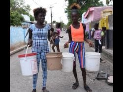 Ian Allen Photo Daniesha Taylor (left) and Shamania Brown with buckets ready to catch water from a pipe.