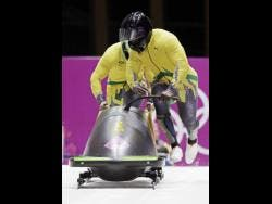 The team from Jamaica JAM-1, piloted by Winston Watts and brakeman Marvin Dixon, start their third run during the men's two-man bobsled competition at the 2014 Winter Olympics in Russia.