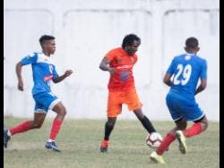 Tivoli Gardens' Rodico Wellington (centre) goes on the attack against opponents from Portmore United in the Red Stripe Premier League at the Spanish Town Prison Oval earlier this season.