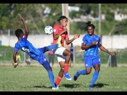 Dunbeholden FC's Kemoy Atkinson (left) gets a toe to the ball ahead of UWI FC's Thorn Simpson, while teammate Shaquille Dyer tracks back during their Red Stripe Premier League game at the UWI Mona Bowl on Sunday, January 12.