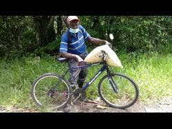 Huecent Spencer, 87, farmer  from Kept district in St Elizabeth, makes his way to his farm after buying a bag of fertiliser.