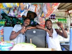 Clifford Blygen (left) and Kemar Salmon have resorted to living in their place of business to keep themselves financially afloat.