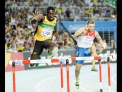 Green (left) clears a hurdle in the preliminary round of the men's 400m hurdles at the World Championships in Daegu in 2011.