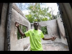 Donovan Morris stands in what is left of his family home which was destroyed by fire.