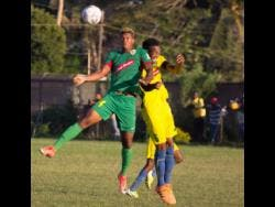 Humble Lion's Andre Clennon (left) jumps for a ball with Vere United's Kenroy Lumsden during their Red Stripe Premier League game at the Wembley Centre of Excellence in Hayes, Clarendon, last  December.