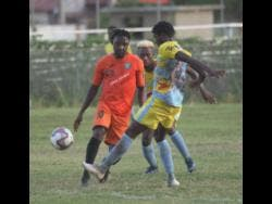Tivoli Garden's Jermaine Johnson makes a pass while  Waterhouse player Colorado Murray  moves in during their  Red Stripe Premier League encounter at the Edward Seaga Sports Complex last December.
