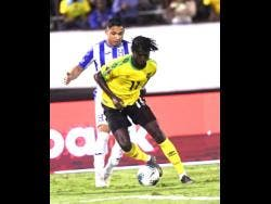 FILE Shamar Nicholson (foreground) dribbles ahead of Honduran player Emilio Izaguirre  in a Concacaf Gold Cup match held at the National Stadium last year.