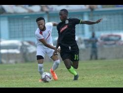 Fakibi Farquharson (right) of Molynes United FC dribbles past  Arnett Gardens FC's Odane Samuels  during a Red Stripe Premier League encounter at the Waterhouse Stadium on September 22 last year.