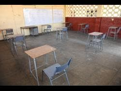 A sparsely furnished secondary school classroom.