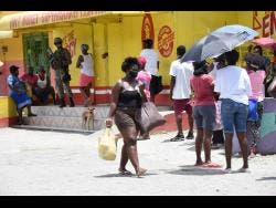Residents of Seaforth in St Thomas line up to purchase goods from a shop after the community was placed under quarantine because of a sharp increase in COVID-19 cases in the community.