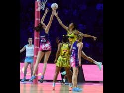 Jamaica goal keeper Shamera Sterling (second right) goes high to defend ahead of Scotland goal shooter Emma Barrie (left), while Jamaica's Adean Thomas (second left) and Lynsey Gallagher (GA) look on during their Vitaly Netball World Cup Group G game at the M&S Bank Arena in Liverpool, England on Wednesday, July 17, 2019.