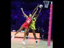 Sunshine Girls captain Jhaniele Fowler (right) outstretches England Rose's goal keeper, Geva Mentor, to claim the ball before scoring a goal during their Group G Vitality Netball World Cup match last year.
