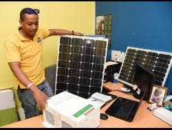 Kevin Mills, renewable energy specialist, owner of REDIS Renewable Energy Design and Installation Services, checks equipment before installation.